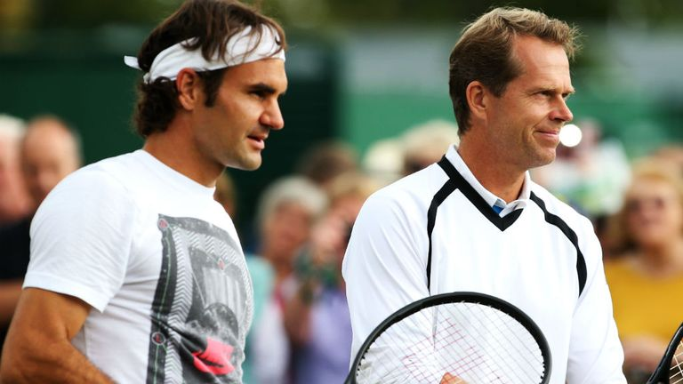 Federer talks with Edberg during a practice session