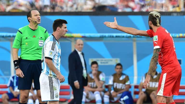 Lionel Messi looks on as Valon Behrami berates referee Jonas Eriksson