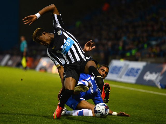 Leon Legge of Gillingham tackles Rolando Aarons of Newcastle