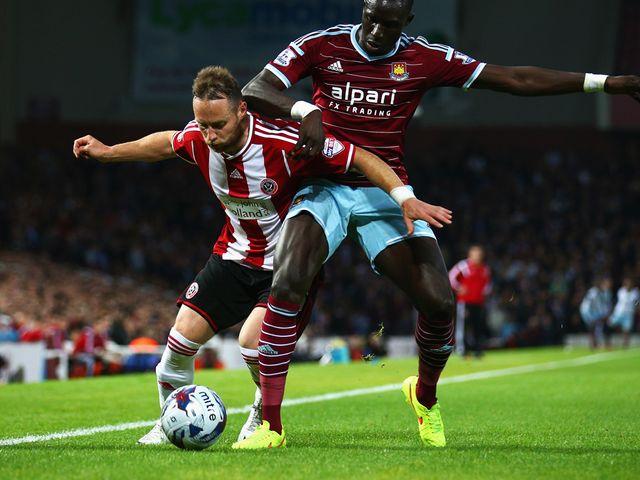 Mohamed Diame of West Ham United challenges Ben Davies