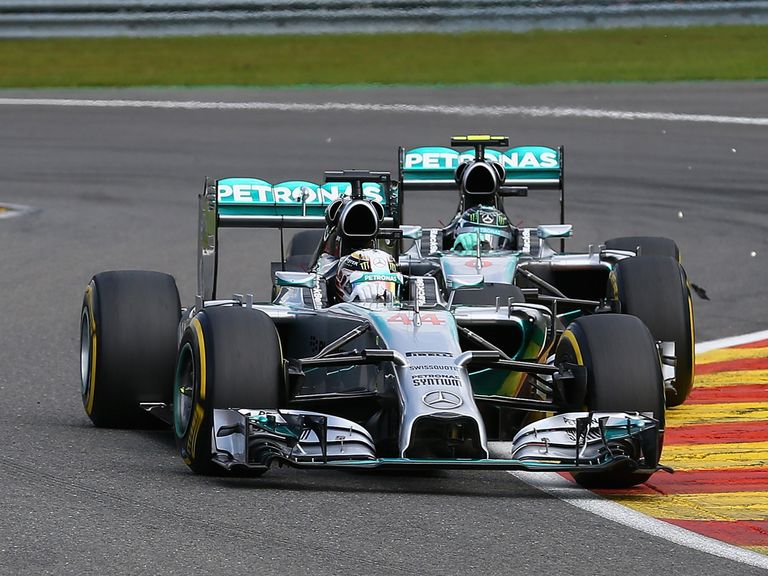 Debris flies in the air after Rosberg makes contact with Hamilton