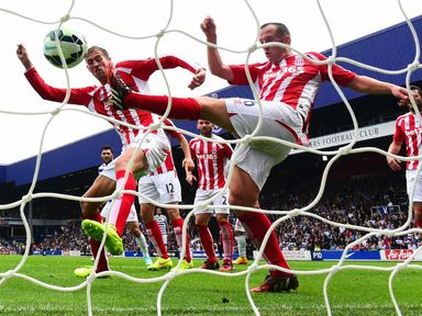 Peter Crouch and Charlie Adam of Stoke City fail to stop Steven Caulker's header on Saturday