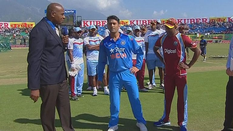 West Indies players line up in solidarity behind Dwayne Bravo (right) at the toss