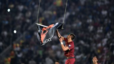 Serbia's defender Stefan Mitrovic grabs a flag with Albanian national symbols flown by a remotely operated drone