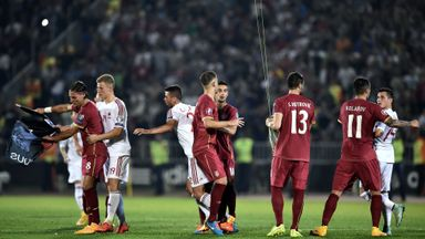 Serbia's and Albania players scuffle over a flag with Albanian national symbols