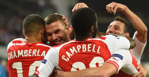 Lukas Podolski is mobbed by his team-mates after his late winner in Brussels