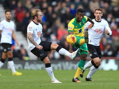 Johnny Russell and Alexander Tettey battle for the ball