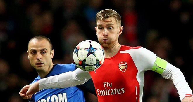 Per Mertesacker controls the ball as Dimitar Berbatov closes him down
