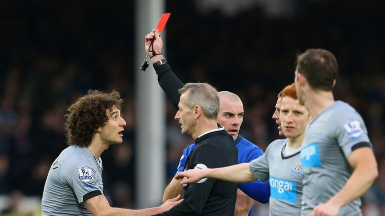 Referee Martin Atkinson shows Fabricio Coloccini a red card