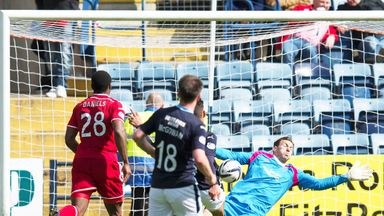 Dundee striker Luka Tankulic lifts the ball over Scott Brown of Aberdeen