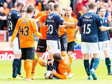 Dundee United striker Nadir Ciftci (ground) beside Jim McAlister