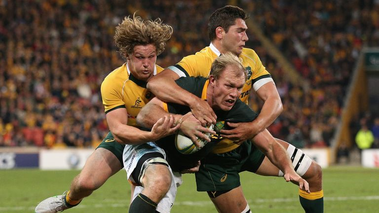 Schalk Burger  is tackled by Michael Hooper and Rob Simmons