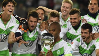 Wolfsburg defender Naldo (C) kisses the trophy and celebrates with his team-mates after winning the German Super Cup