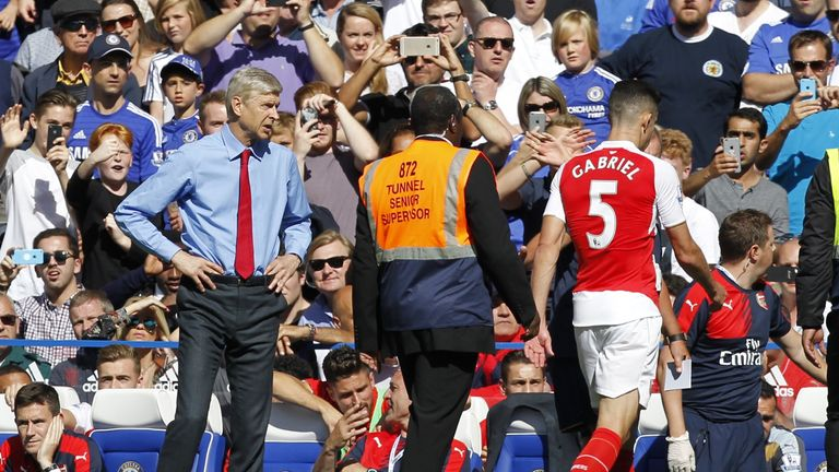 Wenger looks on as Gabriel trudges from the Stamford Bridge field on Saturday