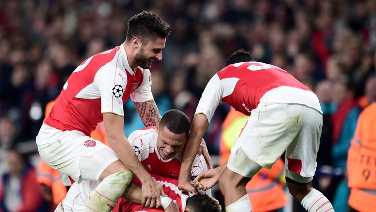 Arsenal's Mesut Ozil is mobbed by team-mates