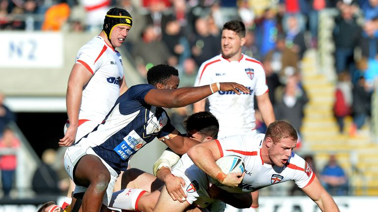 Tom Burgess is tackled by the French defence