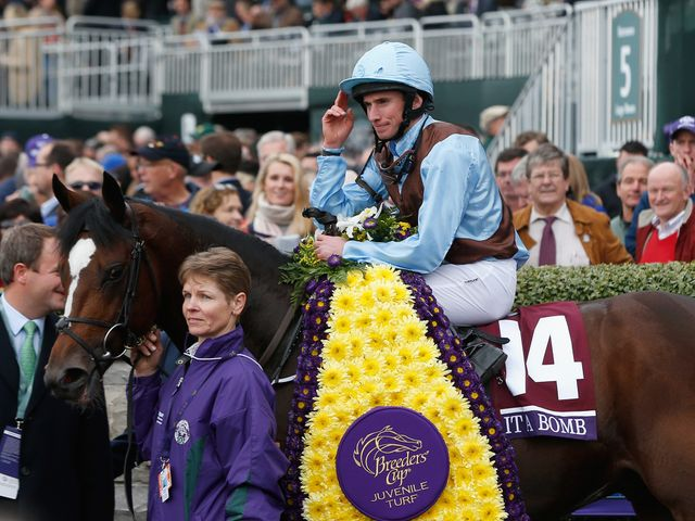 Jockey  Ryan Moore tips his cap in the winners circle after riding Hit It A Bomb to win the Breeder's Cup Juvenile Turf