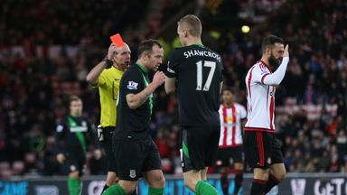 Referee Mike Dean shows Stoke's Ryan Shawcross (second right) a red card