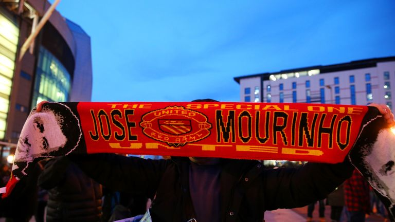 A fan poses with a Manchester United 'Jose Mourinho' scarf