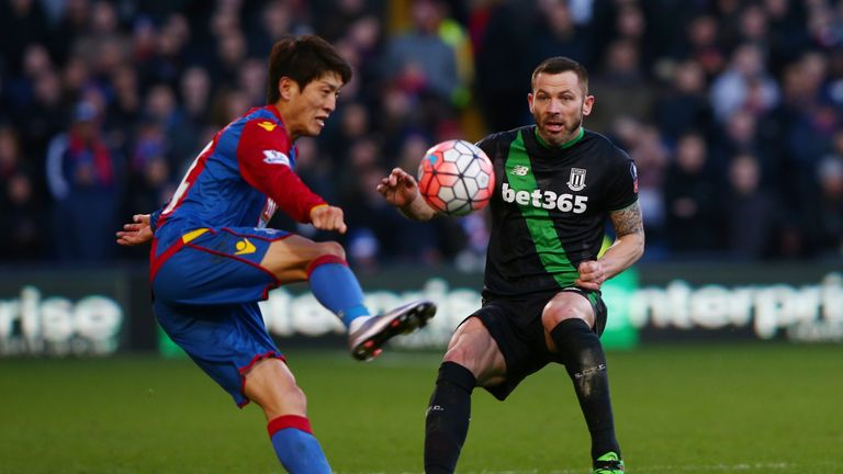 Phil Bardsley of Stoke City and Lee Chung-yong of Crystal Palace compete for the ball