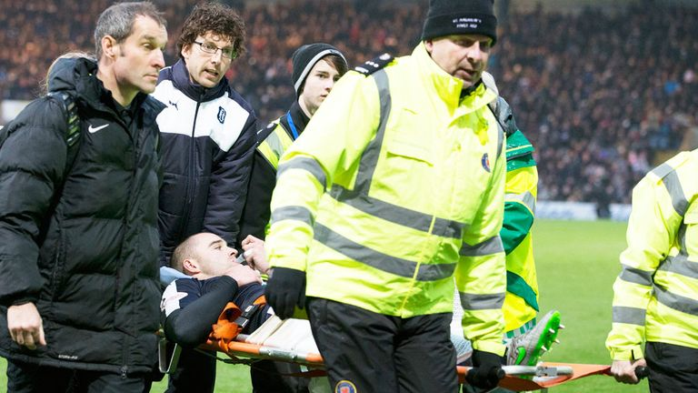 Dundee defender James McPake is carried off after suffering a suspected knee injury