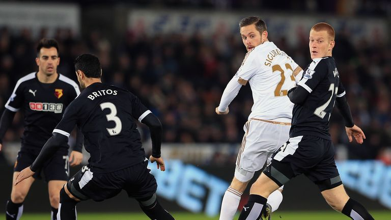Swansea's Gylfi Sigurdsson (centre) battles for the ball