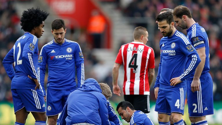 Chelsea's Pedro (centre) receives treatment for a injury