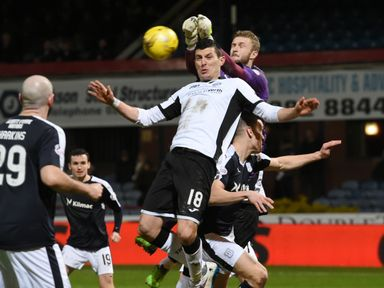 Graham Cummins goes for the ball with Dundee keeper Scott Bain