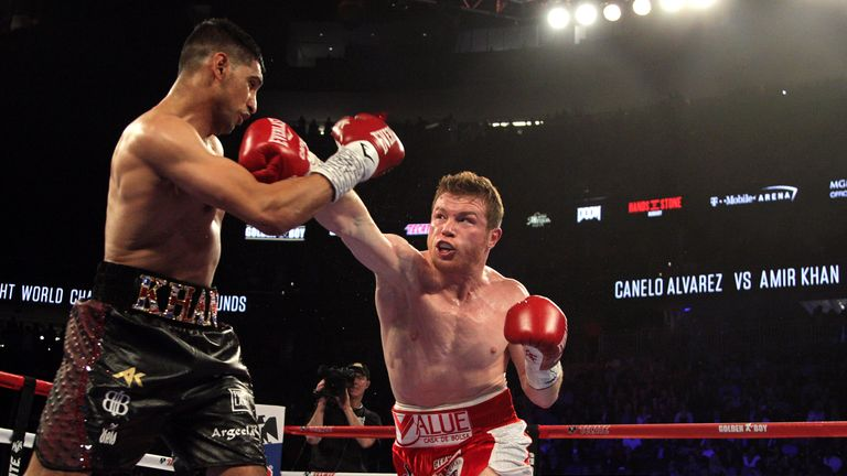 Saul Canelo Alvarez (R) connects a right against Amir Khan (L)