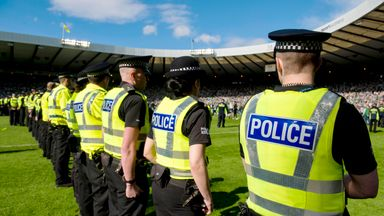 Police line the pitch after the pitch invasion by Hibernian fans following the Scottish Cup final