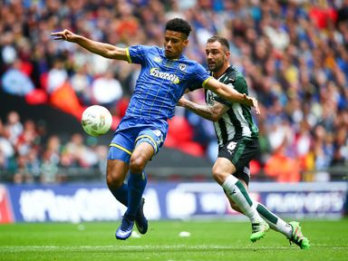 Lyle Taylor of Wimbledon tackles with Carl McHugh of Plymouth during the Sky Bet League Two Play Off Final match between Plymout