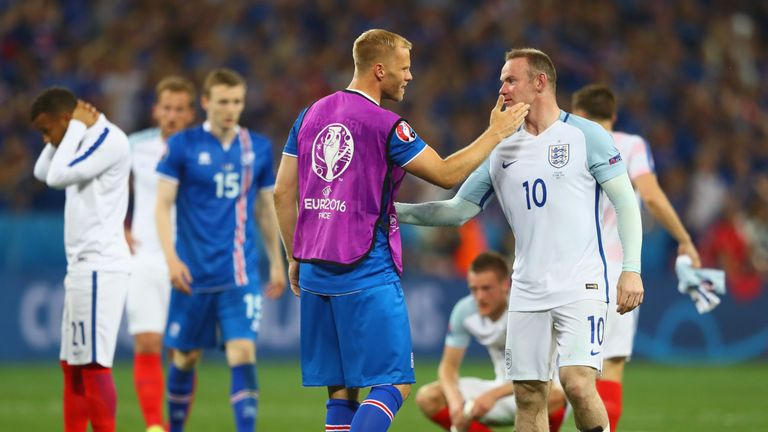 Wayne Rooney is consoled by Eidur Gudjohnsen of Iceland after England's shock defeat