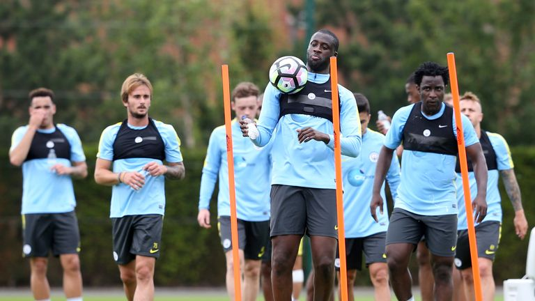Manchester City players wear black vests holding their STATSports Viper pods
