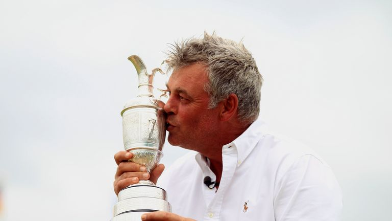 Darren Clarke of Northern Ireland poses with the Claret Jug on the 18th green following his victory in The 140th Open