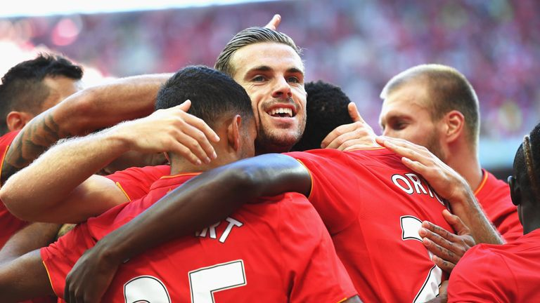 Liverpool players including Jordan Henderson (centre) celebrate the third goal scored by Divock Origi