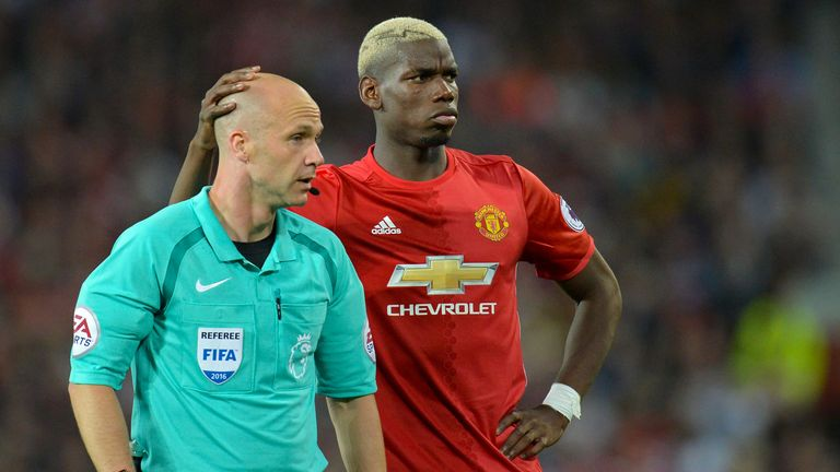 Pogba shares a moment with referee Anthony Taylor