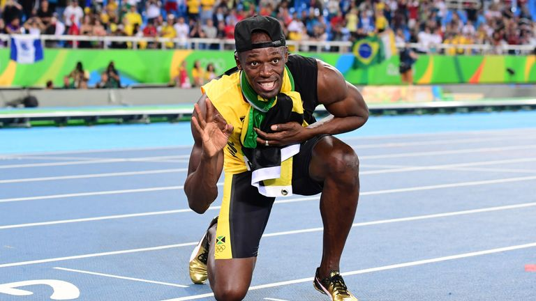 Bolt holds up three fingers after completing the triple triple in Rio