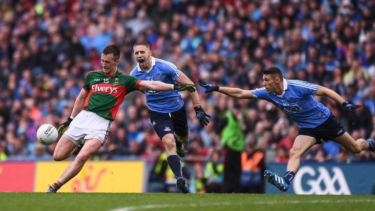 Cillian O'Connor kicks Mayo's equalising point despite the efforts of Dublin's Eoghan O'Gara and Darren Daly