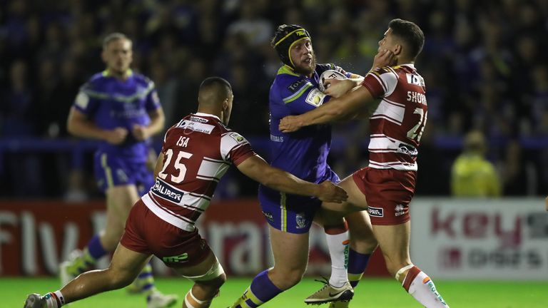 Hill is tackled by Wigan duo Willie Isa (left) and Jake Shorrock (right)