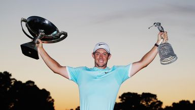Rory McIlroy of Northern Ireland poses with the FedExCup and Tour Championship trophies after his victory over Ryan Moore