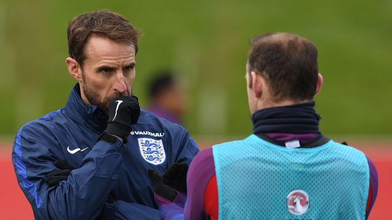 England's Interim manager Gareth Southgate (L) talks with striker Wayne Rooney