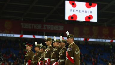 Soldiers hold poppy wreaths ahead of the World Cup Qualifier between Wales and Serbia