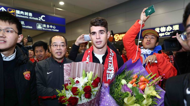 Oscar is escorted as he arrives at Shanghai airport to complete his move to Chinese football