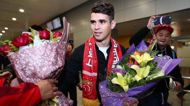 Brazilian football player Oscar receives flowers as he arrives at Shanghai airport