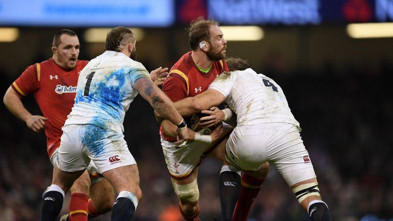 Alun Wyn Jones is tackled by Joe Launchbury (r) and Joe Marler