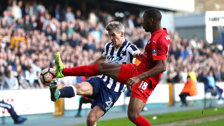 Steve Morison of Millwall (L) clears the ball while under pressure from Molla Wague