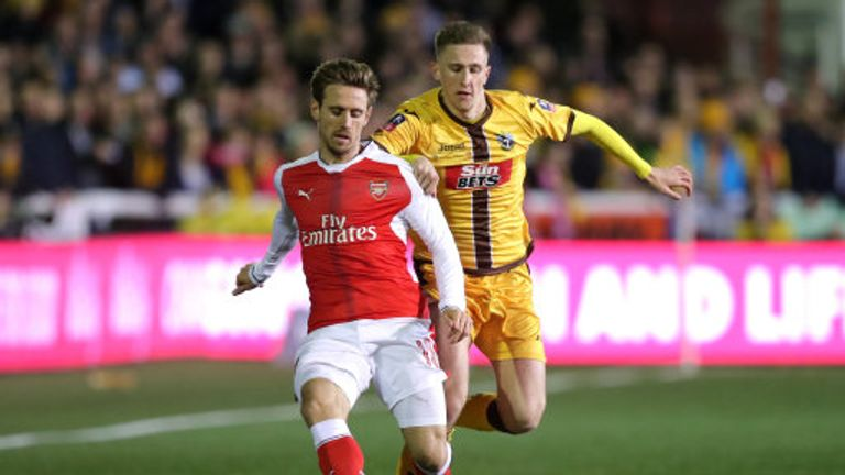 Nacho Monreal and Sutton's Adam May battle for the ball