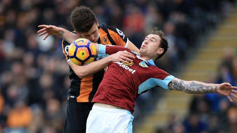 Hull City's Harry Maguire (left) and Burnley's Ashley Barnes battle for the ball during the Premier League match at the KCOM Stadium, Hull.