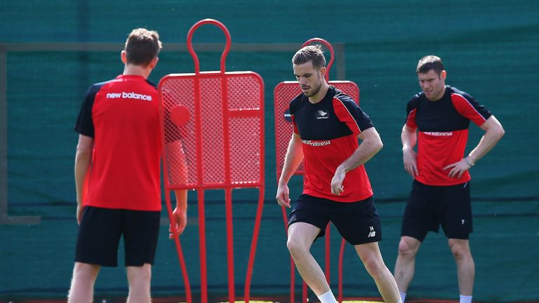 Jordan Henderson runs through a drill while James Milner looks on during a training session at Melwood on May 13, 2016