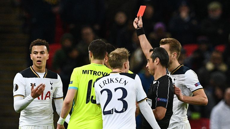 Portuguese referee Jorge Sousa (R) shows a straight red card to send off Tottenham Hotspur's English midfielder Dele Alli (L) during the UEFA Europa League